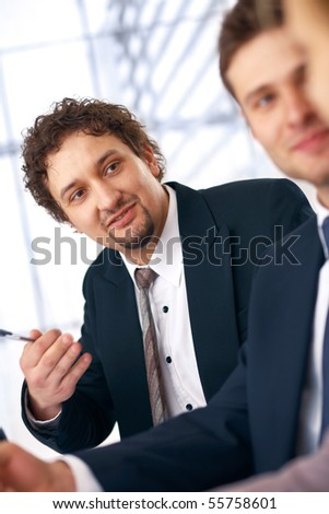 Young smiling businessman on the meeting looking and listening to partners.