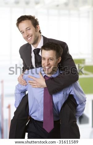 Young smiling businessman piggybacking his colleague - stock photo