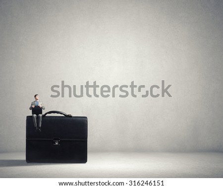 Young smiling businessman sitting on giant briefcase - stock photo