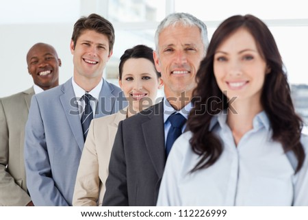 Young smiling businessman standing in a well-lit room among his co-workers