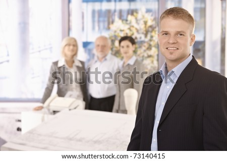 Young smiling businessman standing in office with team in background.? - stock photo