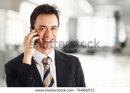 Young smiling businessman talking at phone. Nice bright blurred background.
