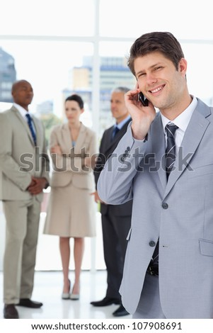 Young smiling businessman using a mobile phone in front of his serious team - stock photo
