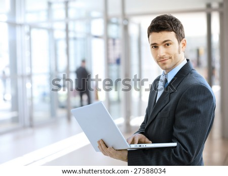 Young smiling businessman using laptop on corporate location, indoor. - stock photo