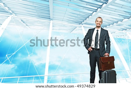 young smiling businessman with bag and modern building background - stock photo