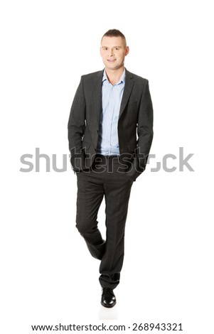 Young smiling businessman with hands in pocket. - stock photo