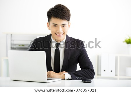young smiling businessman working in office - stock photo