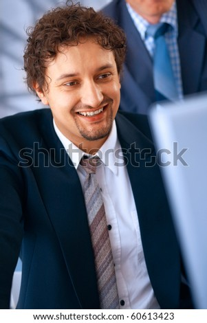 Young smiling businessman working on laptop in the office with his colleague at the back.