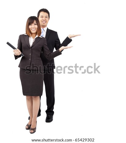 young smiling businesswoman and businessman. with their hand outstretched and presenting something - stock photo