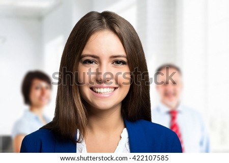 Young smiling businesswoman in front of a group of people