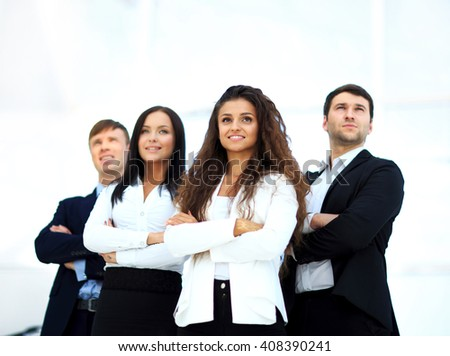 Young smiling businesswoman looking confident while being followed by her colleagues - stock photo