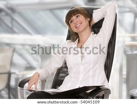 Young smiling businesswoman relaxing on the chair - stock photo