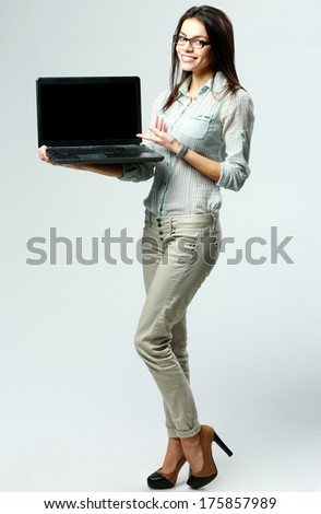 Young smiling businesswoman showing laptop on gray background - stock photo