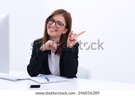Young smiling businesswoman sitting at her workplace in office - stock photo