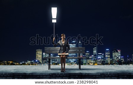Young smiling businesswoman sitting on bench with book on knees
