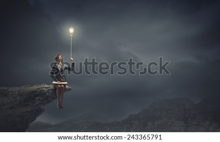 Young smiling businesswoman sitting on rock edge with book in hands - stock photo