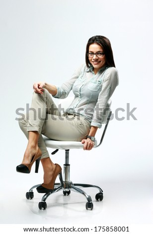 Young smiling businesswoman sitting on the office chair on gray background - stock photo