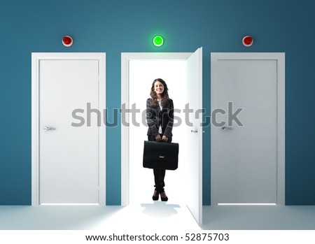 young smiling businesswoman standing infront of the right door - stock photo
