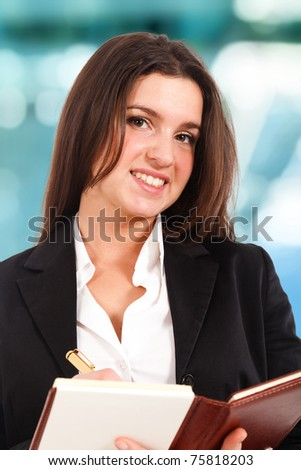 Young smiling businesswoman writing something on her agenda - stock photo