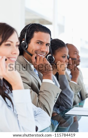 Young smiling call centre worker working among his working team