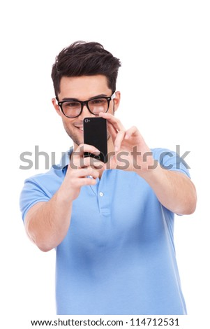 young smiling casual man taking a picture of you with his phone. isolated on white background - stock photo