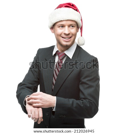 young smiling caucasian businessman in black suit and santa hat pointing at watch isolated on white - stock photo