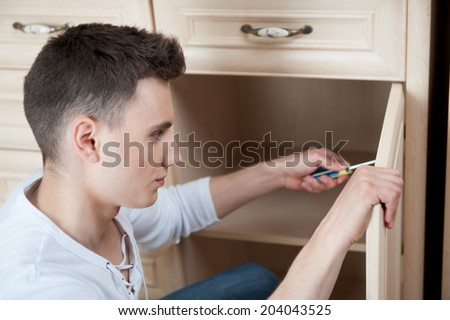 Young smiling caucasian handsome man fixing wooden furniture by screwdriver - stock photo
