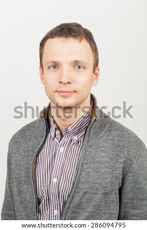 Young smiling Caucasian man in casual clothing, studio portrait over gray background - stock photo