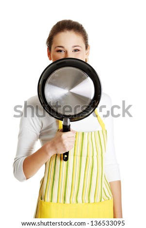 Young smiling caucasian teen girl dressed in apron, smiling behind the frying pan, isolated on white.