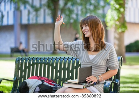 Young smiling college girl waving hand to person outside of image - stock photo