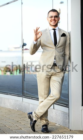 Young smiling confident man doing thumbs up sign outside contemporary office building - stock photo