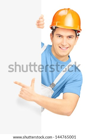 Young smiling construction worker with helmet pointing on a blank panel isolated on white background - stock photo