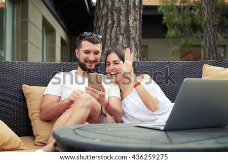 Young smiling couple are sitting on cozy couch on open terrace and conducting a video call on phone, woman waving her hand - stock photo