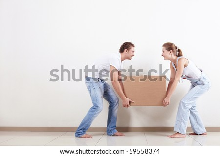 Young smiling couple carries a box - stock photo