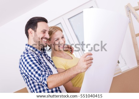 Young smiling couple discussing plan of their new house while holding paper drawing.