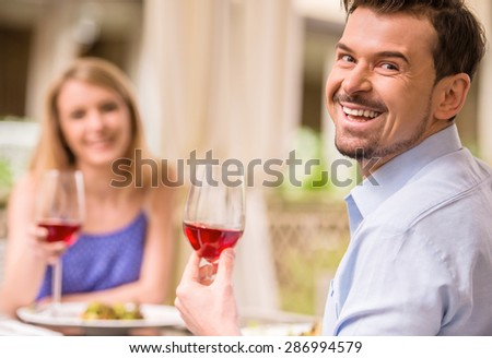 Young smiling couple drinking wine in gorgeous restaurant. - stock photo