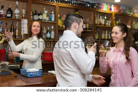 Young smiling couple having a date with wine at bar. Focus on girl