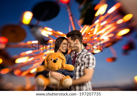 Young smiling couple having a ride on a ferris wheel - stock photo
