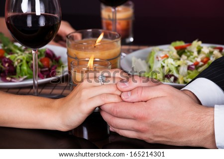 Young Smiling Couple Having Dinner With Wine Glass On Table - stock photo