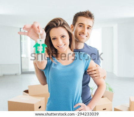 Young smiling couple holding their new house keys, real estate and relocation concept - stock photo