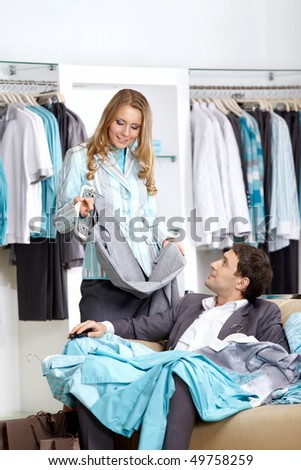 Young smiling couple in shop choose clothes - stock photo