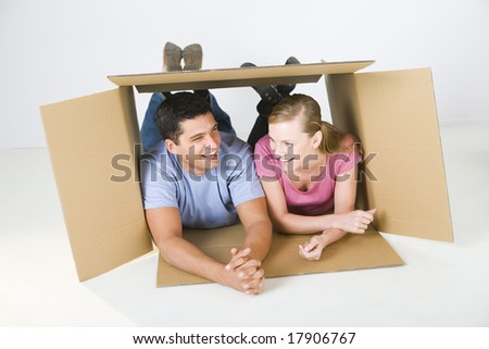 Young smiling couple lying in cardboard box and talking. Front view. - stock photo