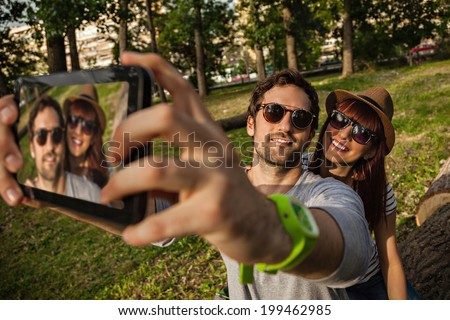 Young Smiling Couple Making A Self Portrait With Digital Tablet. Focus Is On Couple. - stock photo