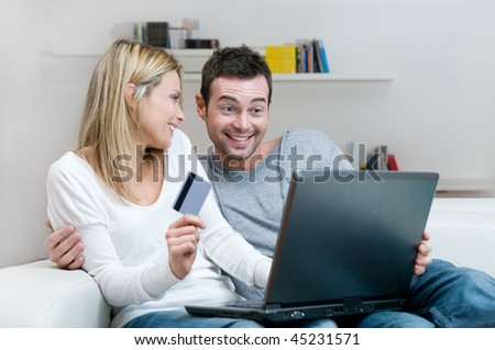 Young smiling couple making shopping online with credit card at home - stock photo