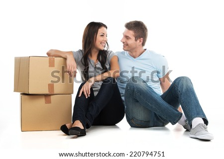 Young smiling couple moving in new house. man and woman sitting on floor and looking at each other.  - stock photo