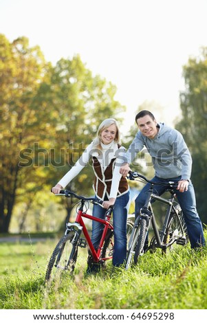 Young smiling couple on bicycles in the park - stock photo
