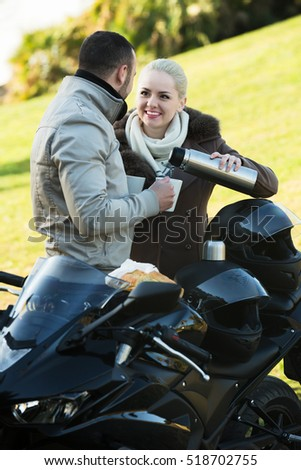 Young smiling couple posing near motorcycle with sandwitches and coffee