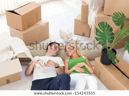 Young smiling couple relaxing in the middle of cardboard boxes - stock photo