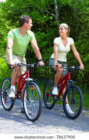 Young smiling couple  riding  in the park - stock photo