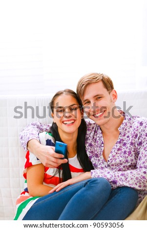 Young smiling couple sitting on couch with mobile